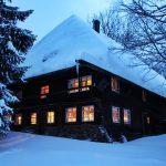 Ferienhaus Außenbereich im Winter: die verschneite Südseite des Häusles am Abend