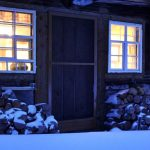 Ferienhaus Außenbereich im Winter: die Küchentür mit golden leuchtenden Fenstern in der Südfassade