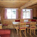 Ferienhaus Erdgeschoss: Holztisch mit Stühlen und Eckbank sowie Couch im Esszimmer