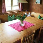 Ferienhaus Erdgeschoss: großer Holztisch mit Eckbank und Stühlen im Esszimmer