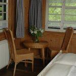 Ferienhaus Obergeschoss: Korbtisch mit Stühlen im weißen Schlafzimmer