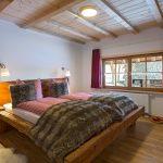 Ferienwohnung Altholzschlafzimmer: rustikales Altholz-Balkenbett mit stilechten Bezügen