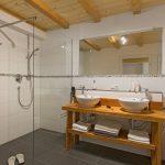 Ferienwohnung Innenräume: Badezimmer mit ebenerdiger Dusche und Altholz-Waschtisch