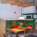 Ferienwohnung Innenräume: Kachelofen mit Altholz-Esstisch und rustikaler Ofenbank sowie schönen Stühlen