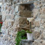 Ferienwohnung Innenräume: Hausflur mit erhaltener Steinwand und Blumennische