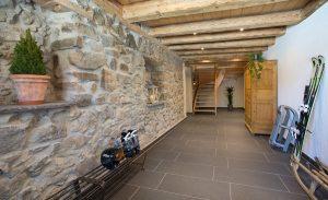 Ferienwohnung Innenräume: weiträumiger Hausflur mit erhaltener Steinwand und Treppenhaus im Winter