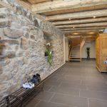 Ferienwohnung Innenräume: weiträumiger Hausflur mit erhaltener Steinwand und Treppenhaus im Sommer