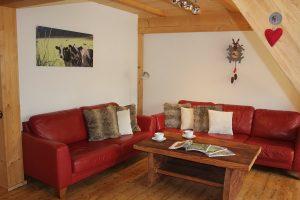 Ferienwohnung Innenräume: Wohnbereich mit gemütlichen Ledersofas, Flachbild-TV und Altholz-Couchtisch