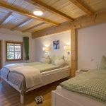 """Ferienwohnung Innenräume: das """"weiße"""" Schlafzimmer mit edlem Doppelbett, Einzelbett und Nachttischen sowie Balkon-Zugang"""