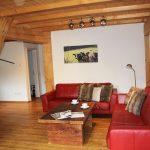 Ferienwohnung Innenräume: Wohnbereich mit Ledersofas, Altholz-Tisch und Flachbild-TV