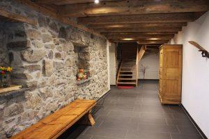 Der Flur zum Treppenhaus der Ferienwohnung: ausgestattet mit rustikaler Holzbank, traditionellem Bauernschrank und dezenter Deko