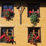 Griesbachhof: renovierte Fassade mit Blumenschmuck und Jesuskreuz