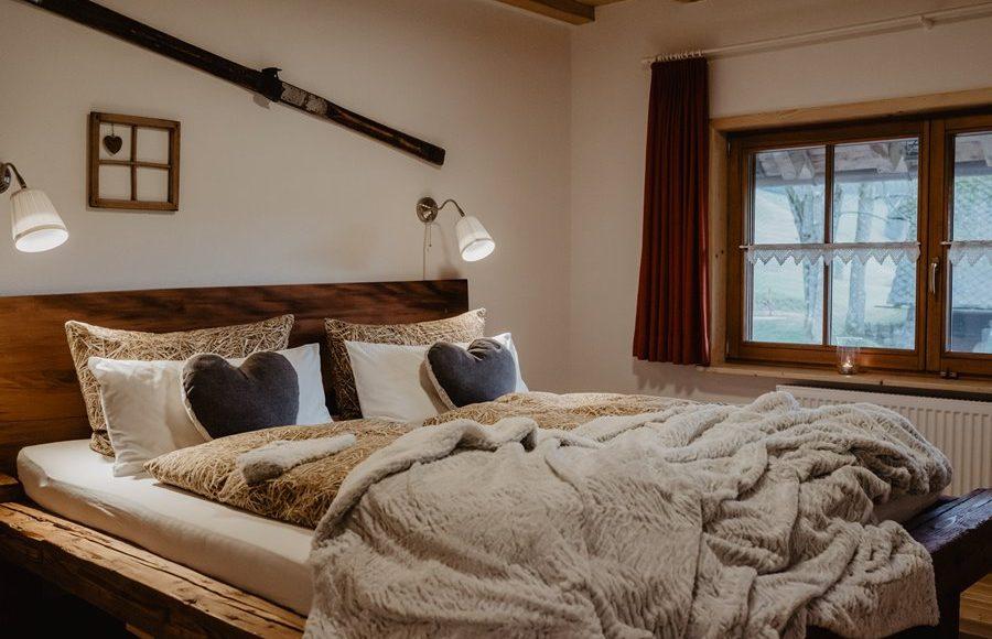 schlafzimmer-mit-altholzbett-Ferienwohnung-im-Heustock-Griesbachhof-Schwarzwald